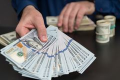 Man offering a bribe or payoff of 100 USD bills stock photos
