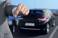 Man offering a car key to the observer. A man in a gray suit offering a car key to the observer, with a car in the background Royalty Free Stock Images