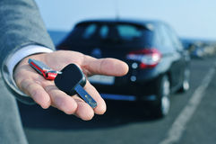 Man offering a car key to the observer. Man in suit offering a car key to the observer, with a car in the background Stock Images