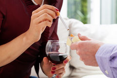 Man offering a cigarette. Man offering woman holding glass with wine a cigarette Stock Image