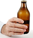 Man offering cold brown bottle of beer, over white Stock Image