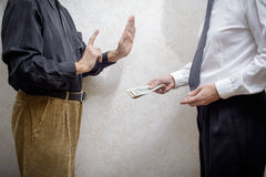Man Offering  a Dollars bribe to a Man Refusing it Stock Photo