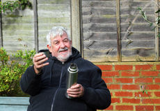 Man offering a drink from a vacuum flask. Stock Image