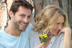 Man offering flowers. Man offering women wild flowers Stock Photography