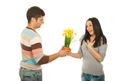 Man offering flowers to amazed woman. Man offering daffodils flowers in pot to amazed women isolated onw hite background Stock Photography