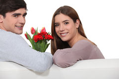 Man offering flowers to girlfriend Royalty Free Stock Images