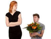 Man offering flowers to his angry girlfriend royalty free stock photography
