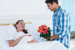 Man offering flowers to pregnant woman in hospital. Man offering flowers to pregnant women lying in bed in hospital Stock Photography