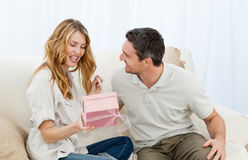 Man offering a gift to his wife royalty free stock images