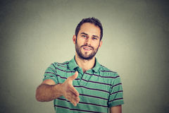 Man offering handshake isolated on gray wall background Stock Images