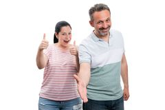 Man offering handshake and woman holding thumbs up. Trustworthy men offering handshake as greeting or deal and women holding thumbs up like gesture isolated on royalty free stock image