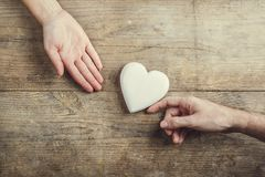 Man offering a heart to a woman. Royalty Free Stock Images