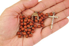 Man is offering or holding rosary with his hand on Stock Photography