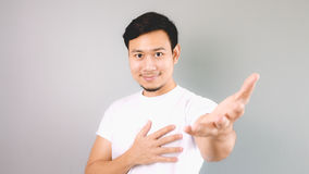 A man offering love from his heart. An asian man with white t-shirt and grey background stock images