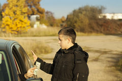 Man offering money from car Royalty Free Stock Image
