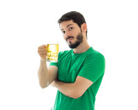 Man is offering a mug of bier. Wearing green clothes. Royalty Free Stock Photography
