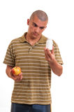 Man offering pill in one hand and apple in another. Royalty Free Stock Images