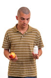 Man offering pill in one hand and apple in another. Stock Images