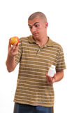 Man offering pill in one hand and apple in another. Stock Photography