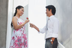 Man offering a red rose to girlfriend. On the stairs Stock Photos