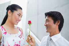 Man offering a red rose to girlfriend. On the stairs Royalty Free Stock Photography