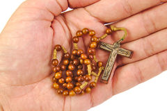 Man is offering rosary with his hand on a white. Man is offering rosary with his hand on white background Royalty Free Stock Images