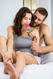 Man offering a rose to woman on bed Stock Photography