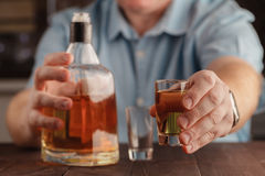 Man offering some shot of alcohol as a solution to your problems Stock Photo