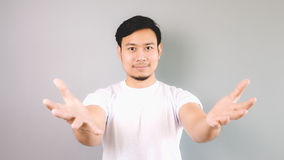 A man offering something. An asian man with white t-shirt and grey background stock images