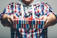 Man Offering Stripe Gift Box with Red Ribbon Royalty Free Stock Photos