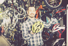 Man offers a choice of helmets for cyclists Royalty Free Stock Images