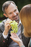 Man offers grapes to woman Stock Photography