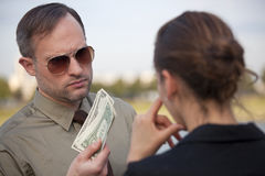 Man offers money to woman Royalty Free Stock Photos