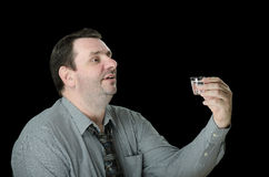 Man offers a toast with vodka. Mature short haired man offers a toast with shot of vodka on black background Royalty Free Stock Image
