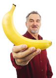 Man offers a yellow banana with outstretched arm Royalty Free Stock Photography