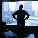 Man in office. Middle-aged Caucasian male with hands on his hips in office with skyline in background