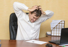 The man in the office angrily grabs his head. The man at the desk in the office angrily grabs his head royalty free stock photo