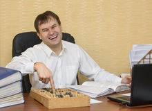 A man in an office aughing pointing at an abacus. A man in an office at a desk laughing pointing at an abacus Royalty Free Stock Images