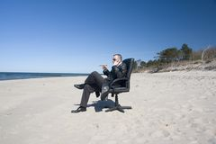 Man in Office Chair on Beach royalty free stock photos