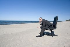 Man in Office Chair on Beach royalty free stock photo