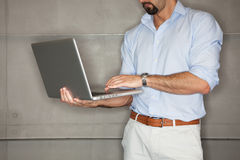 Man in office checking his presentation on laptop. Royalty Free Stock Photography