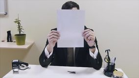 Man in the office closes face with paper. Office worker covers her face with a sheet of paper from his superiors stock footage