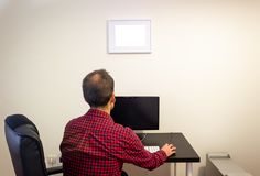 Man at Office Computer on Wooden Black Desk Mockup. Dotted Red Shirt, LCD Screen, Keyboard, Mouse, Desktop Computer, Photo Frame, stock images