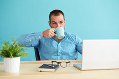 Man in office drinking coffee Royalty Free Stock Images
