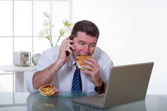 Man at office eat unhealthy food. Man at office with phone eat unhealthy food stock image