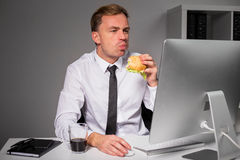 Man at the office eating burger Stock Photos