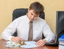 The man in the office, filling a notice of an accident with the money and the machine lying on the documents. On the table royalty free stock photo