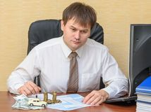 The man in the office, filling a notice of an accident with the money and the machine lying on the documents. On the table stock photos