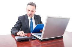 Man at office holding clipboard and calculating. Man wearing suit at office holding clipboard and calculating isolated on white background Stock Photography