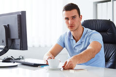 Man in office holding coffee. Young man in office holding coffee cup Royalty Free Stock Photography